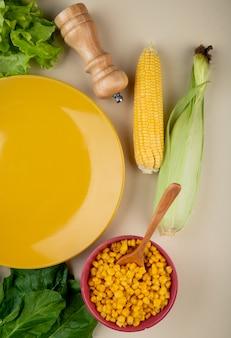 Vista superior de sementes de milho cozido com espigas de milho espinafre e alface com prato vazio em branco