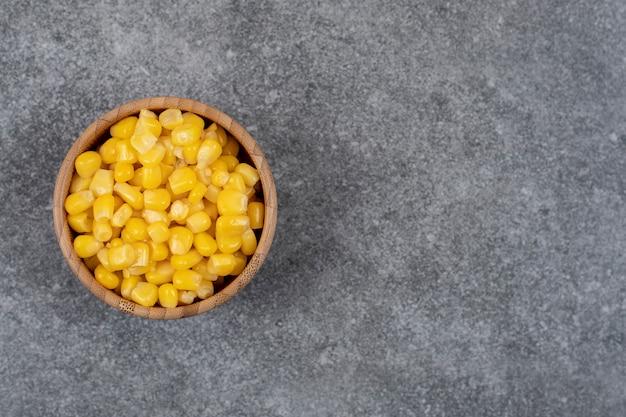 Vista superior de sementes de milho doce em conserva em uma tigela de madeira