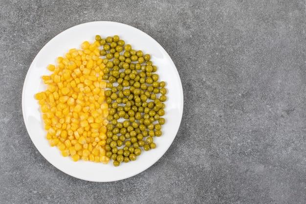 Vista superior de sementes de milho em lata e ervilha verde na chapa branca
