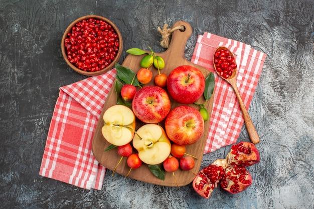 Vista superior de sementes de romã colher o tabuleiro de maçãs cerejas na toalha de mesa