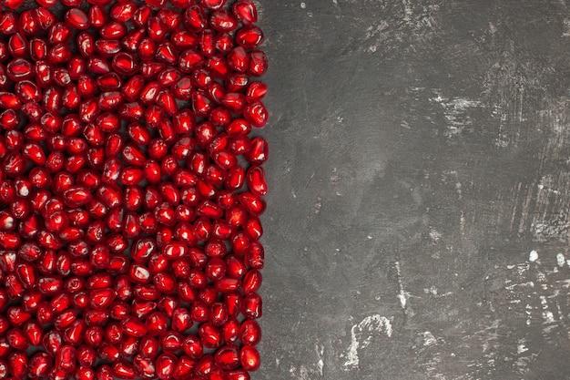 Vista superior de sementes de romã em formato retangular em superfície escura