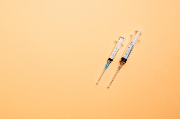 Vista superior de seringas médicas em superfície colorida