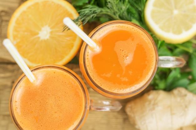 Vista superior de smoothies de cenoura em canecas de vidro com laranja e limão.