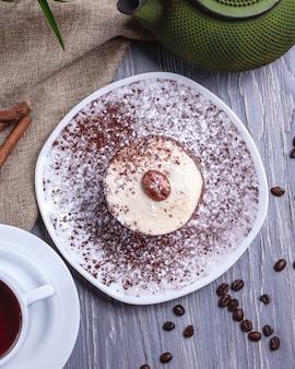 Vista superior de sobremesa de chocolate com creme e café em grão