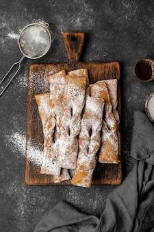 Vista superior de sobremesas de açúcar em pó com peneira