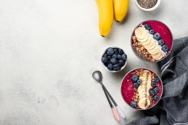 Vista superior de sobremesas de café da manhã em tigelas com bananas e colheres