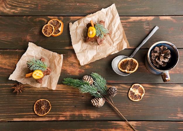 Vista superior de sobremesas doces com pinhas e frutas cítricas secas
