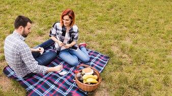 Vista superior, de, sorrindo, par jovem, tocando, com, cartões, ligado, cobertor, em, piquenique