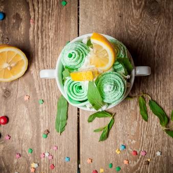 Vista superior de sorvete de hortelã com folhas de limão e hortelã na xícara