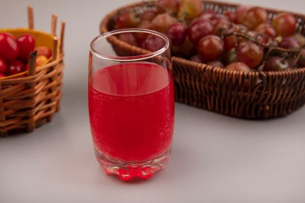 Vista superior de suco de cereja fresco em um copo com uvas em um balde em uma parede cinza