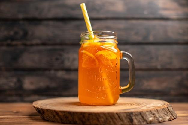 Vista superior de suco de laranja fresco em um copo com tubo em uma bandeja de madeira em fundo marrom