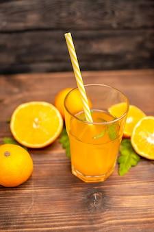 Vista superior de suco de laranja fresco em um copo servido com tubo de hortelã e laranjas inteiras cortadas em uma mesa de madeira