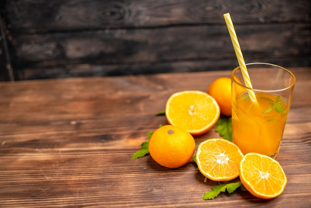 Vista superior de suco de laranja fresco em um copo servido com tubo de hortelã e laranjas inteiras cortadas no lado esquerdo em uma mesa de madeira