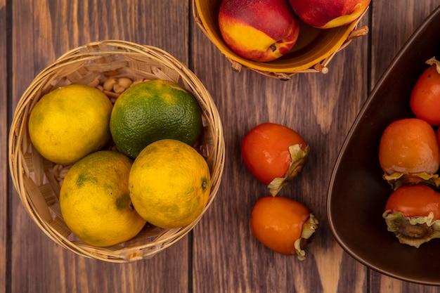 Vista superior de suculentas tangerinas maduras em um balde com caquis isolados em uma parede de madeira