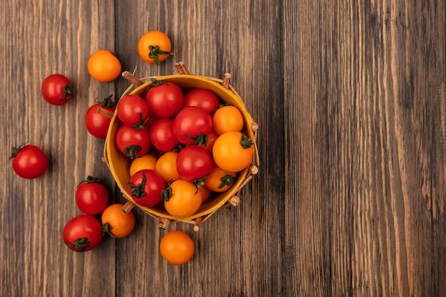 Vista superior de suculentos tomates cereja vermelhos e laranja em um balde com tomates isolados em uma parede de madeira com espaço de cópia