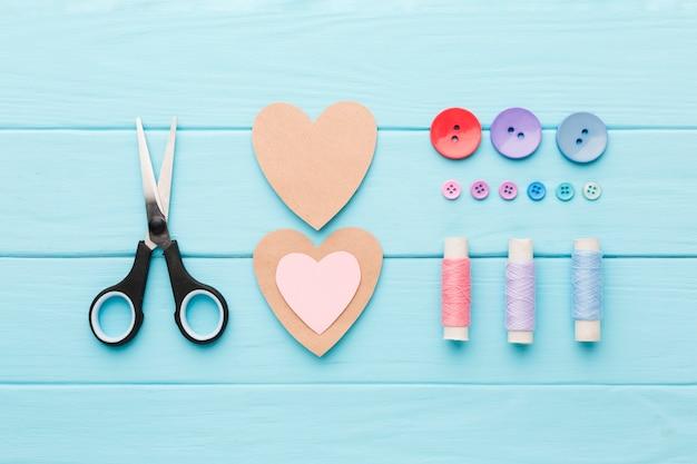 Vista superior de suprimentos de costura com corações de papel para dia dos namorados