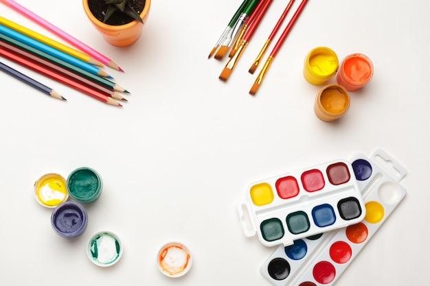 Vista superior de suprimentos de pintura em aquarela, pincéis e lápis colorido. processo de criação de pintura em aquarela. copie o espaço.