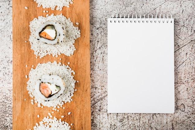 Vista superior de sushi rola na bandeja de madeira com o bloco de notas em branco em espiral sobre fundo rústico