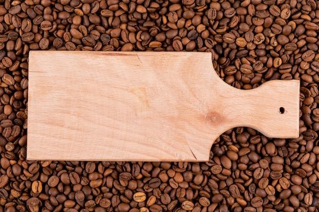 Vista superior de tábua de madeira na superfície dos grãos de café