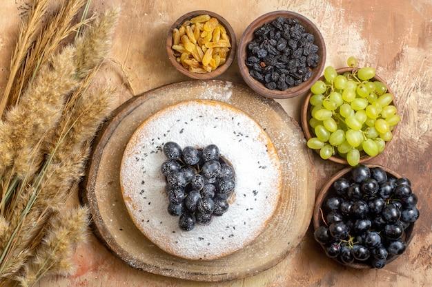 Vista superior de taças de uvas de uvas verdes e pretas, passas e espigas de bolo na mesa
