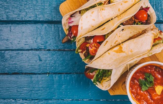 Vista superior de tacos mexicanos; molho de salsa com carne e legumes na tábua de cortar