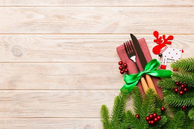 Vista superior de talheres amarrado com fita no guardanapo em madeira, decorações de natal e renas, ano novo