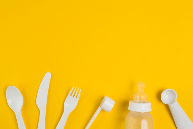 Vista superior de talheres de plástico e mamadeira para chá de bebê