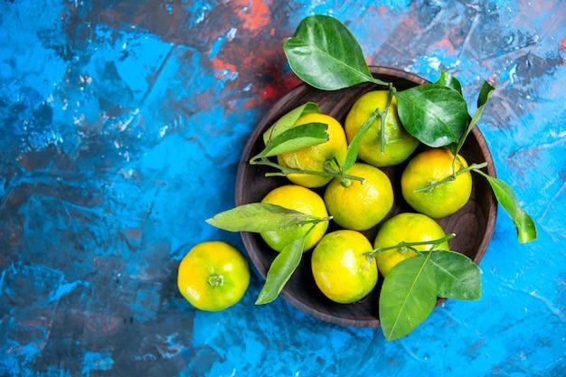Vista superior de tangerinas amarelas com folhas em uma tigela de madeira no espaço livre de superfície azul