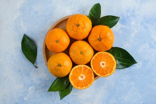 Vista superior de tangerinas de clementina com folhas em uma placa de madeira