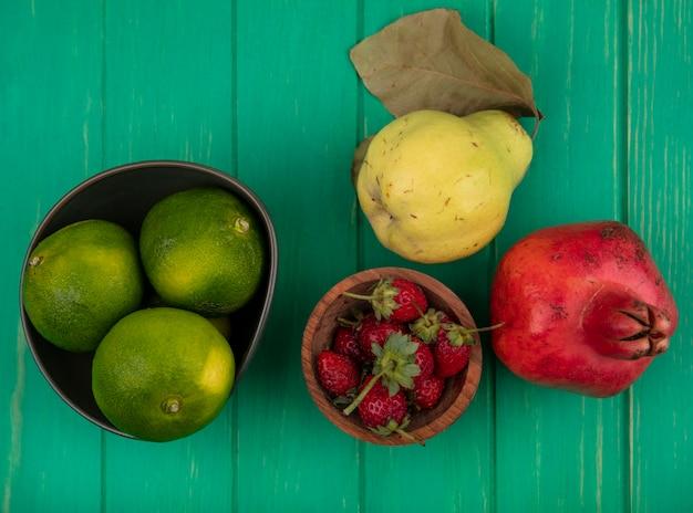 Vista superior de tangerinas em uma tigela e pêra romã e morangos