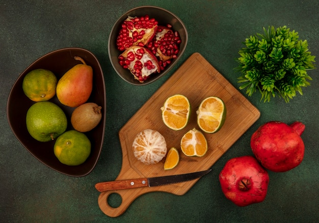 Vista superior de tangerinas frescas abertas e cortadas ao meio em uma placa de cozinha de madeira com uma faca com romãs abertas em uma tigela
