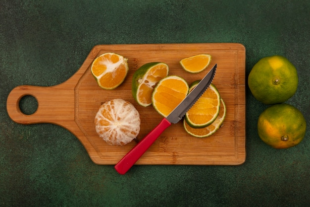 Vista superior de tangerinas frescas abertas e cortadas ao meio em uma placa de cozinha de madeira com uma faca com tangerinas inteiras isoladas