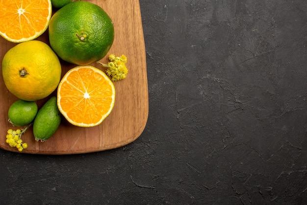 Vista superior de tangerinas frescas com feijoa no preto
