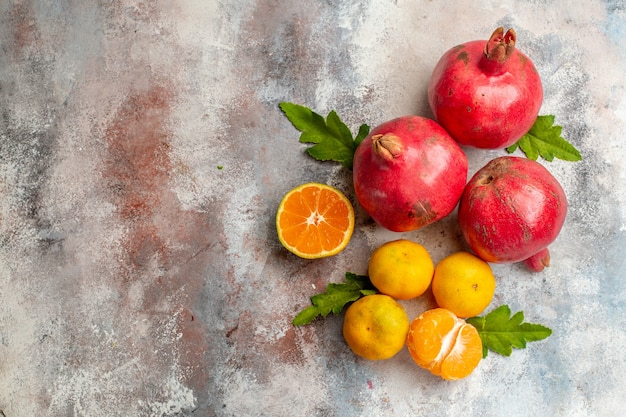 Vista superior de tangerinas frescas com romãs em um fundo claro