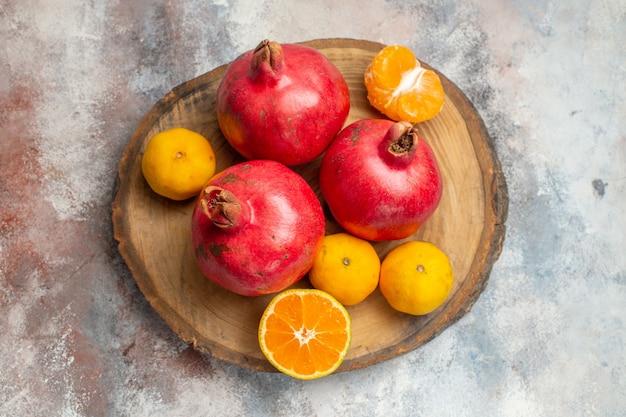 Vista superior de tangerinas frescas com romãs vermelhas em fundo claro