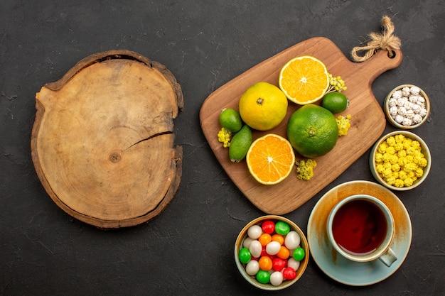 Vista superior de tangerinas frescas com uma xícara de chá e doces no preto