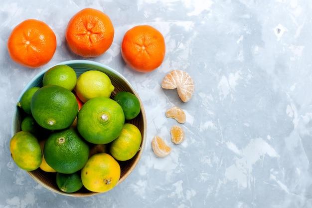 Vista superior de tangerinas frescas e ácidas com limões na mesa branca clara