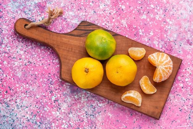 Vista superior de tangerinas frescas e ácidas na superfície rosa