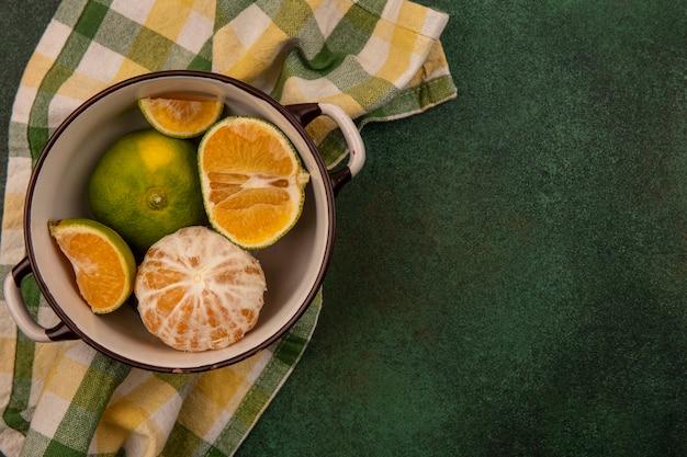 Vista superior de tangerinas frescas e saudáveis em uma tigela em um pano xadrez com espaço de cópia