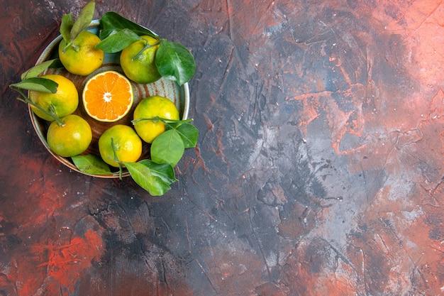 Vista superior de tangerinas frescas em superfície vermelha escura com espaço de cópia