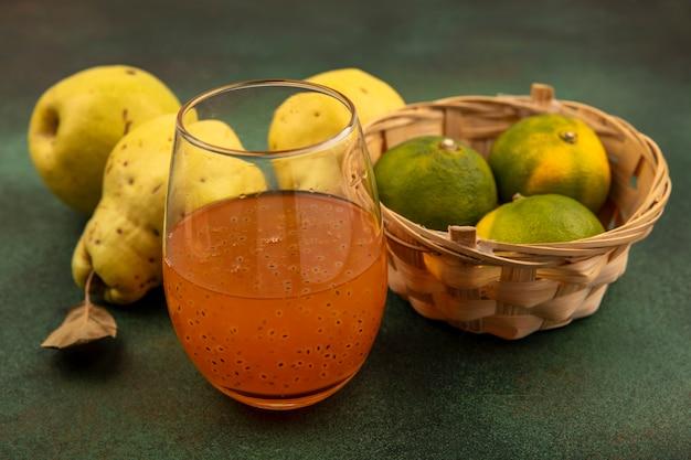 Vista superior de tangerinas frescas em um balde com marmelos e um copo de suco de frutas frescas