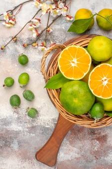 Vista superior de tangerinas frescas em uma cesta de vime em uma tábua de corte em um fundo nu