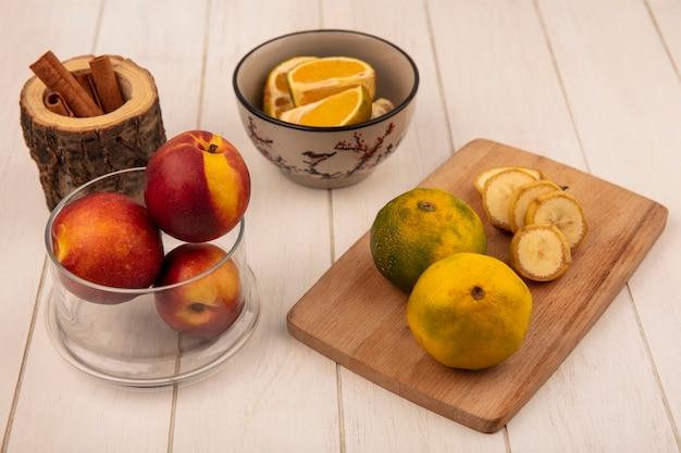Vista superior de tangerinas frescas em uma placa de cozinha de madeira com rodelas de banana com pêssegos em uma tigela de vidro em uma superfície de madeira branca