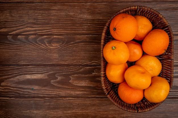 Vista superior de tangerinas frescas maduras em uma cesta de vime na madeira com espaço de cópia