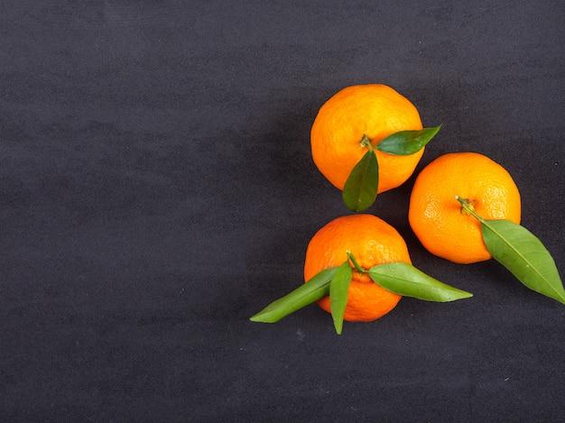 Vista superior de tangerinas frescas na superfície preta