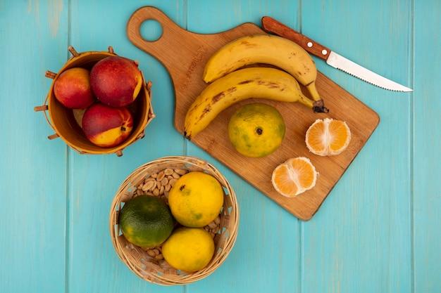 Vista superior de tangerinas inteiras e meias frescas em uma placa de cozinha de madeira com bananas e uma faca com pêssegos em um balde em uma parede de madeira azul
