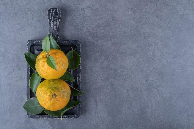 Vista superior de tangerinas orgânicas na placa de madeira preta.