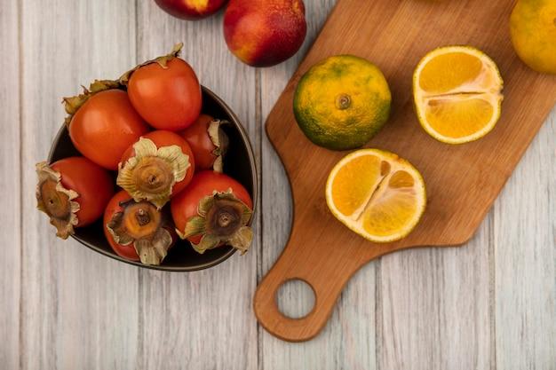 Vista superior de tangerinas saudáveis em uma placa de cozinha de madeira com caquis em uma tigela com pêssegos isolados em uma parede de madeira cinza
