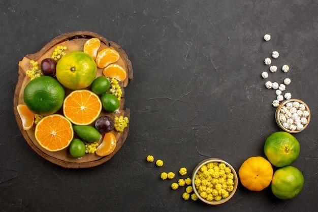 Vista superior de tangerinas verdes frescas com feijoas e doces no escuro