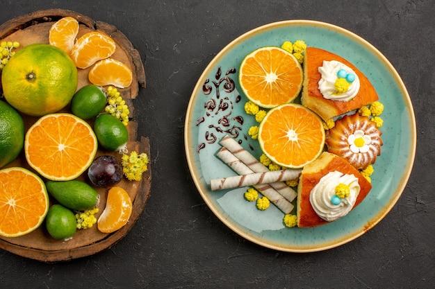 Vista superior de tangerinas verdes frescas com feijoas e fatias de bolo no escuro